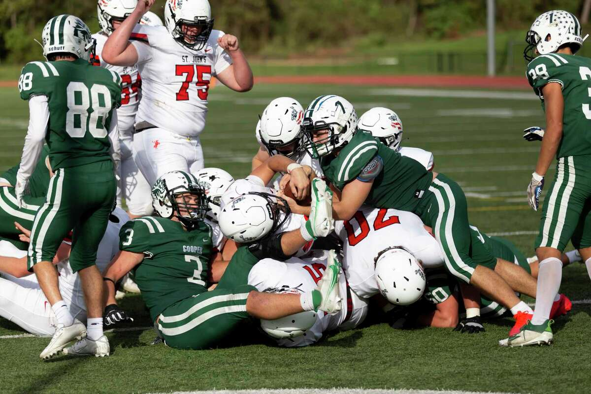 St. John's quarterback John Perdue (11) is dogpiled at the end zone during the third quarter of a SPC football game held at The John Cooper School, Saturday, Nov. 14, 2020, in The Woodlands.