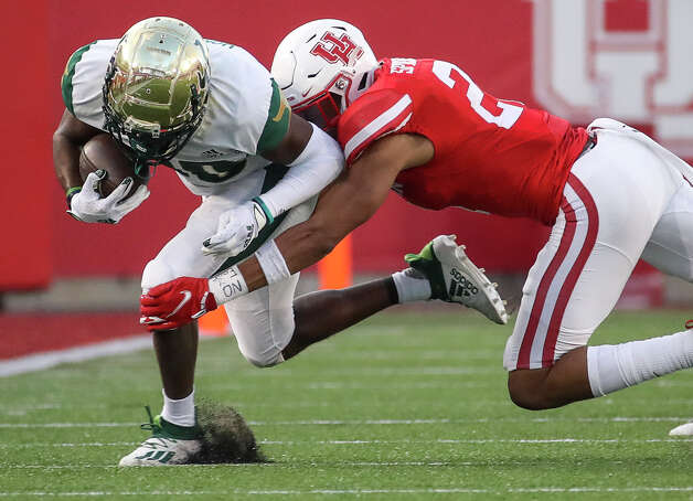 South Florida Bulls wide receiver Terrence Horne (80) is tackled by Houston Cougars safety Gleson Sprewell (21) after a catch and run during the third quarter of an NCAA football game Saturday, Nov. 14, 2020, at TDECU Stadium in Houston. Photo: Jon Shapley/Staff Photographer / © 2020 Houston Chronicle