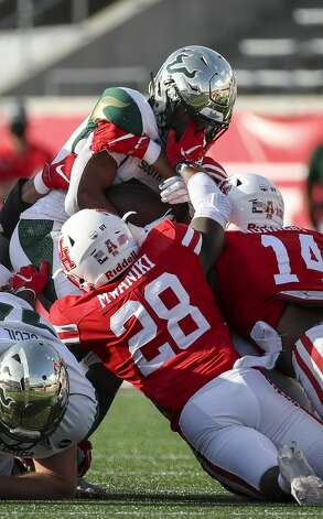 South Florida Bulls running back Brian Battie (21) gets stopped by Houston Cougars safety Thabo Mwaniki (28) and linebacker Mannie Nunnery (14) during the second quarter of an NCAA football game Saturday, Nov. 14, 2020, at TDECU Stadium in Houston. Photo: Jon Shapley/Staff Photographer / © 2020 Houston Chronicle