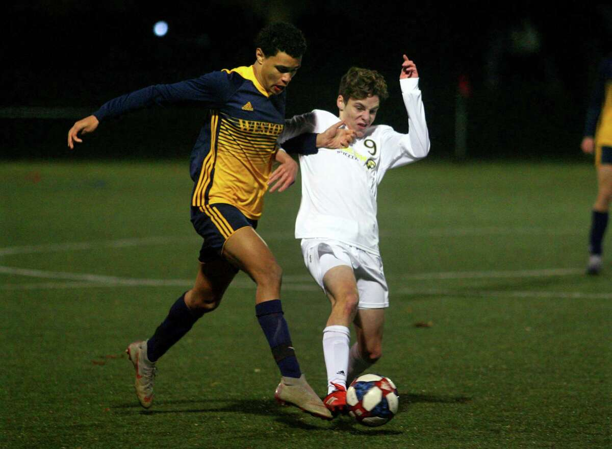 Weston's Jordan Blunschi, left, tries to fend off Joel Barlow's Rice Davis as he works the ball during SWC South Boys Soccer championship action in Weston, Conn., on Saturday Nov. 14, 2020.