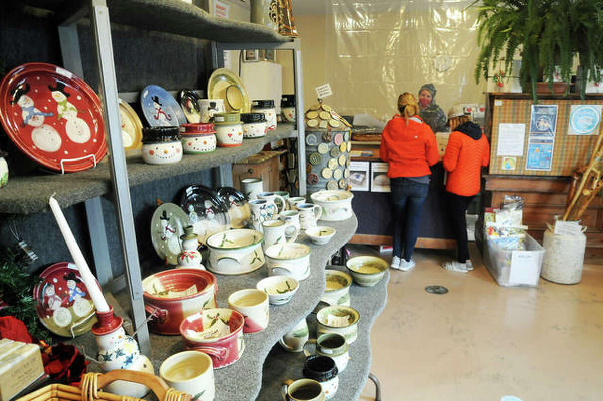 Mississippi Mud Pottery owner Felicia Breen makes a sale on Saturday.