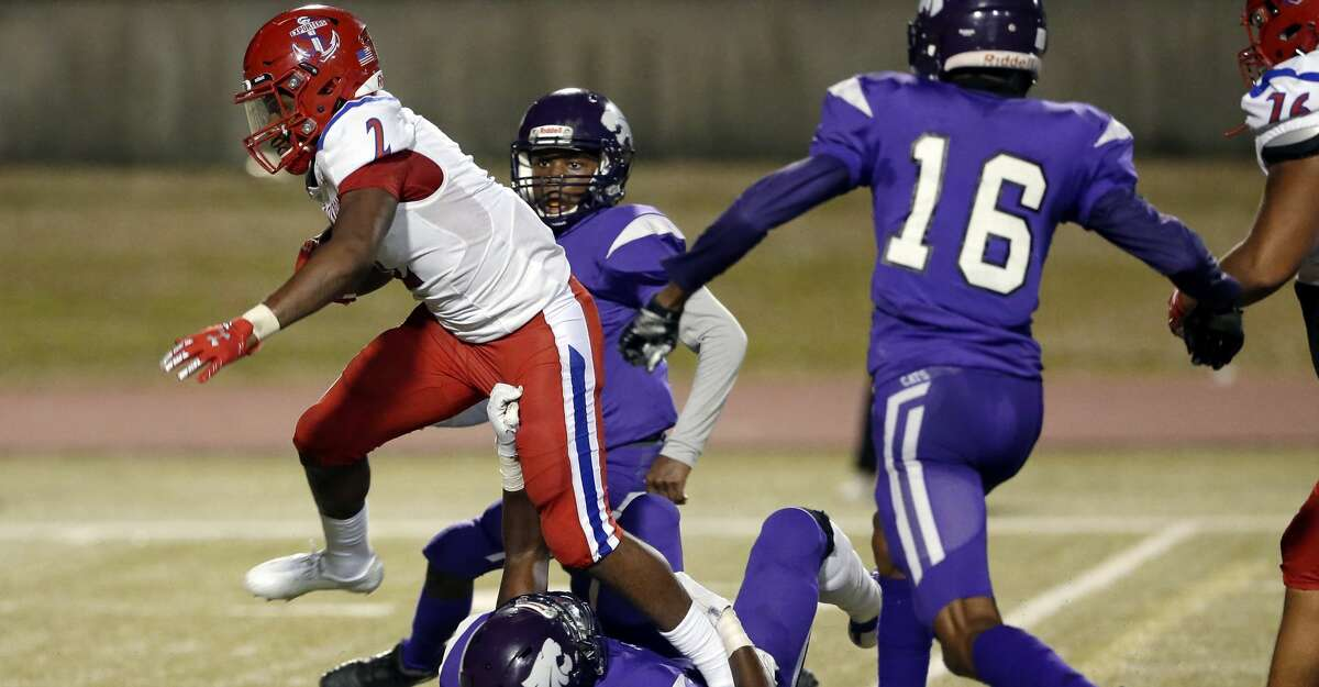 Brazosport Exporters' Paul Woodard (2) breaks the tackle attempt by Wheatley Wildcats linebacker Davion Bouldwin, bottom, during the first half of a high school football game at Barnett Stadium Saturday, Nov. 14, 2020 in Houston, TX.