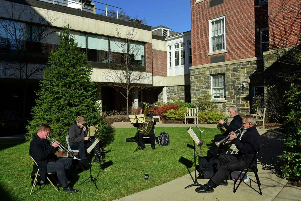 Jerry Bryant, Cliff Haynes, Morris Kainuma, Peter Reit and James Hamlin of The Greenwich Symphony Orchestra Brass Quintet perform a special outdoor concert at The Nathaniel Witherell for senior residents and staff Saturday, November 14, 2020, in Greenwich, Conn. The performance was outdoors and residents and staff enjoyed the concert through the facility's courtyard windows The Witherell, which is owned and operated by the town of Greenwich, is restricting visitors because of the spread of the coronavirus.