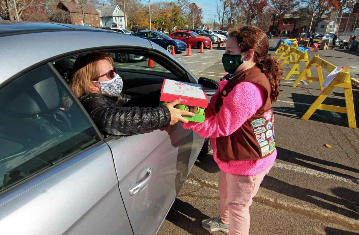 Girl scout Claire Bozso, 8, with Troop 30320, grabs a food donation from Kim Hoagland, of Milford, during the 16th Annual Thanks-for-Giving Food Drive at Wasson Field parking lot in Milford, Conn., on Saturday Nov. 14, 2020. Stop & Shop teamed up with Milford area Boy and Girl Scouts to receive food donations as well as give out packaged Thanksgiving Day foods, including a turkey of course. According to Laffaldano, a food donation was also given to several local food pantries and charities.