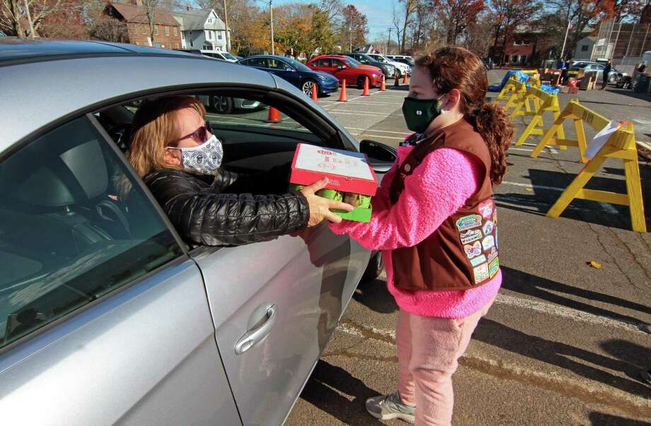 Girl scout Claire Bozso, 8, with Troop 30320, grabs a food donation from Kim Hoagland, of Milford, during the 16th Annual Thanks-for-Giving Food Drive at Wasson Field parking lot in Milford, Conn., on Saturday Nov. 14, 2020. Stop & Shop teamed up with Milford area Boy and Girl Scouts to receive food donations as well as give out packaged Thanksgiving Day foods, including a turkey of course. Photo: Christian Abraham / Hearst Connecticut Media / Connecticut Post
