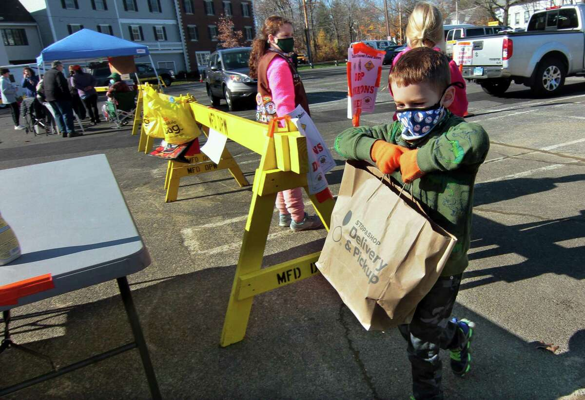 Connor Bozso , 5, carries a food donation during the 16th Annual Thanks-for-Giving Food Drive at Wasson Field parking lot in Milford, Conn., on Saturday Nov. 14, 2020. Connor came to help out his sister, girl scout Claire Bozso, 8, with Troop 30320. Stop & Shop teamed up with Milford area Boy and Girl Scouts to receive food donations as well as give out packaged Thanksgiving Day foods, including a turkey of course. Additionally, a contactless food collection was held Thursday at Milford Public Schools.