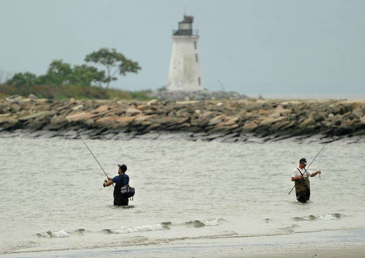 Fishermen wade in the surf of the Sound off Seaside Park in Bridgeport, Conn. on Wednesday, September 6, 2017. Fayerweather Island, marked by its lighthouse, is also a popular spot for fishing.