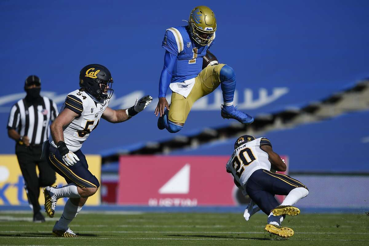 UCLA quarterback Dorian Thompson-Robinson leaps over Cal's Josh Drayden as linebacker Evan Tattersall pursues. Thompson-Robinson had 52 rushing yards and 196 through the air.