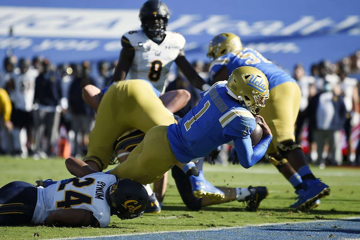 UCLA quarterback Dorian Thompson-Robinson, right, runs in for a touchdown while being tackled by California cornerback Camryn Bynum during the first half of an NCAA college football game in Los Angeles, Sunday, Nov. 15, 2020. (AP Photo/Kelvin Kuo)
