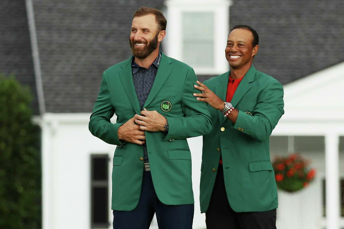 AUGUSTA, GEORGIA - NOVEMBER 15: Dustin Johnson of the United States is awarded the Green Jacket by Masters champion Tiger Woods of the United States during the Green Jacket Ceremony after winning the Masters at Augusta National Golf Club on November 15, 2020 in Augusta, Georgia.