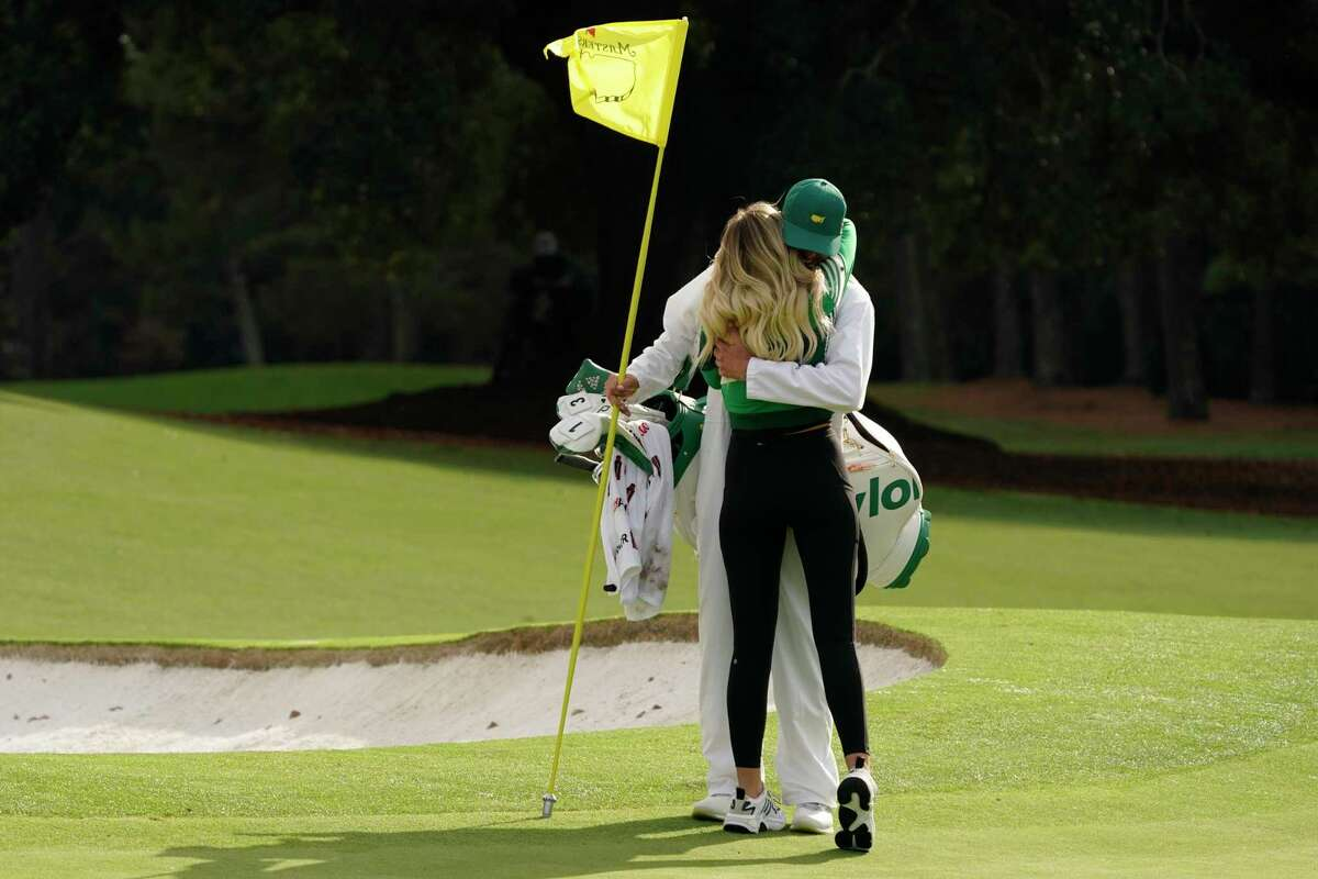 Dustin Johnson's wife Paulina Gretzky hugs his caddie and brother Austin after Dustins victory at the Masters golf tournament Sunday, Nov. 15, 2020, in Augusta, Ga. (AP Photo/Charlie Riedel)