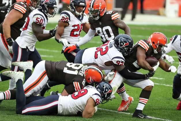 Cleveland Browns running back Nick Chubb (24) fights for yardage as he is caught from behind by Houston Texans defensive end J.J. Watt (99) and nose tackle Brandon Dunn (92) during the third quarter of an NFL football game at FirstEnergy Stadium Sunday, Nov. 15, 2020, in Cleveland. Photo: Brett Coomer, Staff Photographer / © 2020 Houston Chronicle