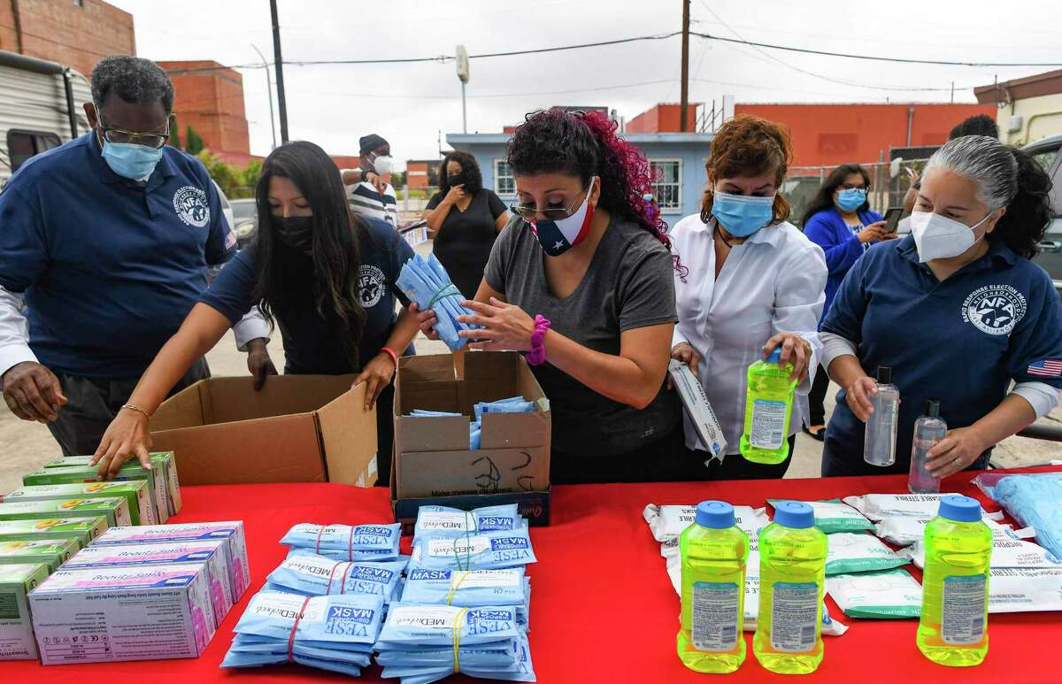 MEDwheels CEO Jane Gonzalez, second from right, and others pack a box of masks, disinfectant and other items to be donated to Neighborhoods First Alliance on Thursday, Nov. 12, 2020. Since the start of the coronavirus pandemic, Gonzalez's small business has donated personal protective equipment to churches, school districts and medical personnel across San Antonio.