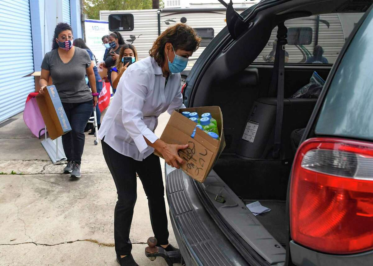 MEDwheels CEO Jane Gonzalez loads box containing masks, disinfectant and other items into a van destined for Neighborhoods First Alliance on Thursday, Nov. 12, 2020. The items, donated by Gonzalez's small business, will be distributed at a blood drive later this week.