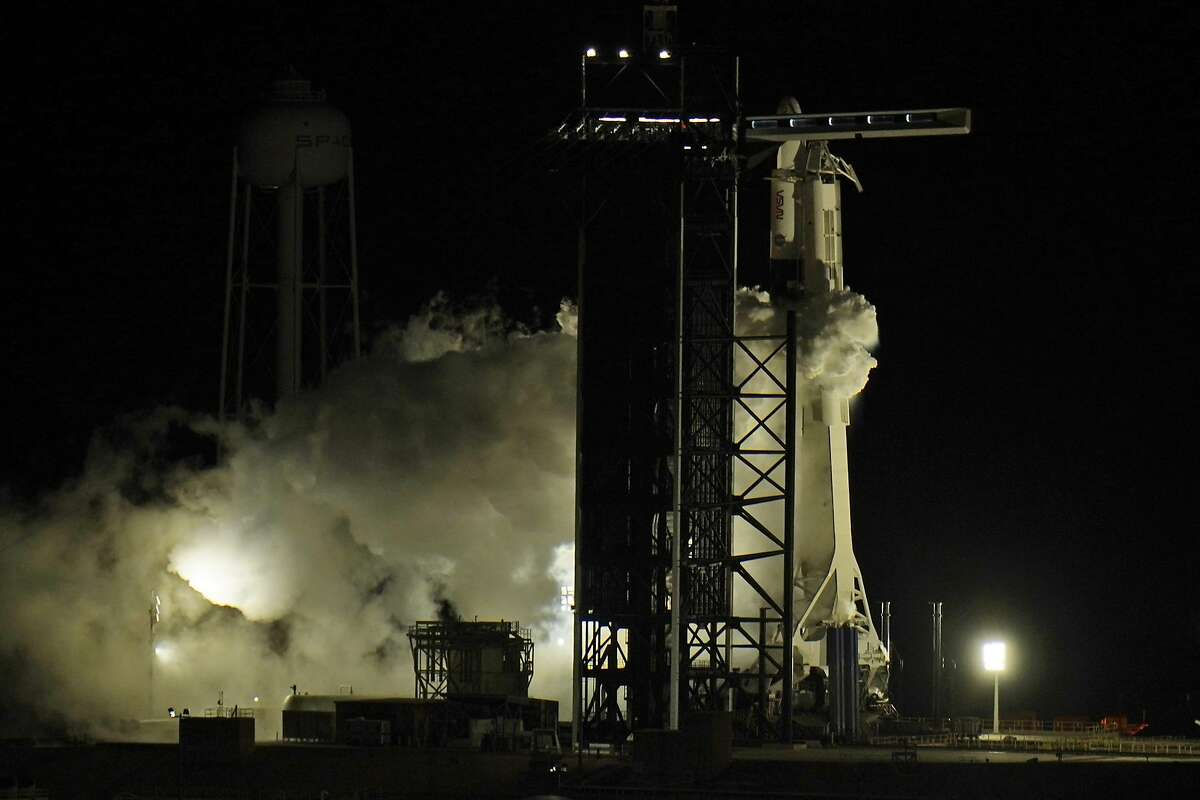 Fuel is purged from the SpaceX Falcon9 rocket, with the Crew Dragon capsule attached, as it sits at the Kennedy Space Center's Launch Complex 39-A for an evening launch Sunday Nov. 15, 2020, in Cape Canaveral Fla. The crew is headed to the International Space Station. (AP Photo/Chris O'Meara)