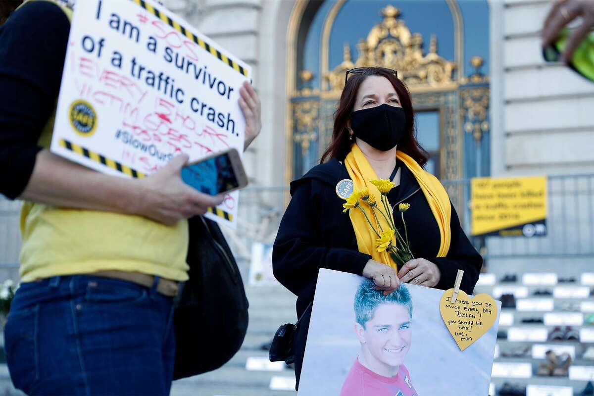 Julie Mitchell of Clayton holds a sign memorializing her son, Dylan, during World Day of Remembrance for Road Traffic Victims. The San Francisco event included 187 pairs of shoes and placards commemorating the number of dead on San Francisco streets since 2014.
