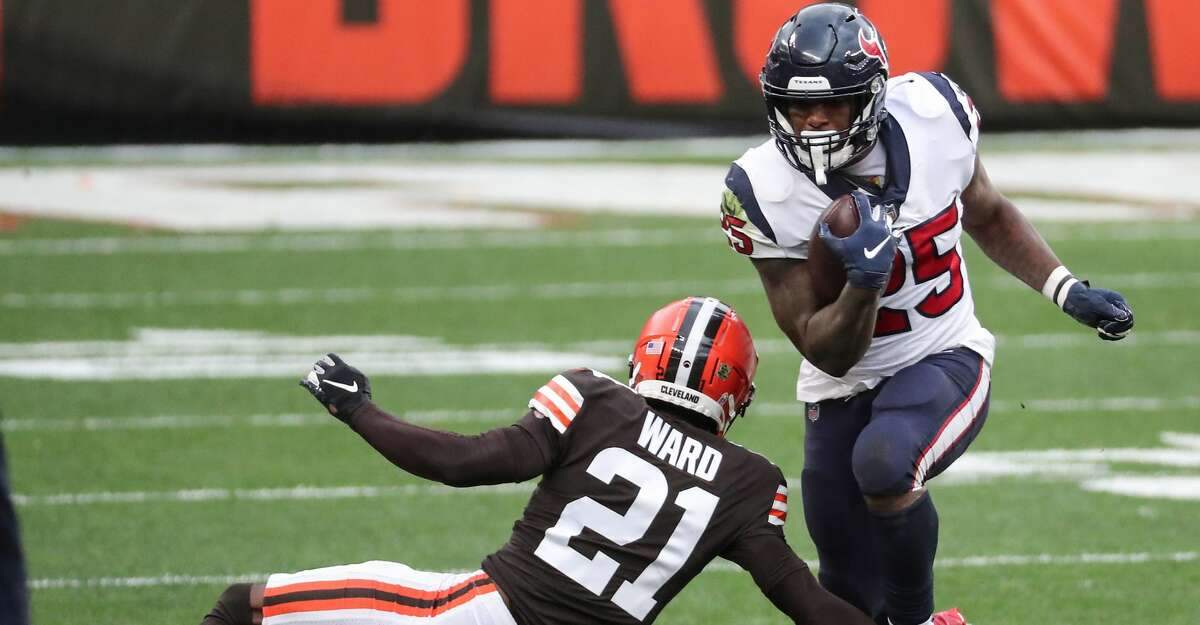 Houston Texans running back Duke Johnson (25) is tripped up by Cleveland Browns cornerback Denzel Ward (21) during the first half of an NFL football game at FirstEnergy Stadium Sunday, Nov. 15, 2020, in Cleveland.