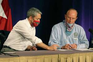 Mayor Ron Nirenberg and Bexar County Judge Nelson Wolff look over information before a city-county briefing on the coronavirus. In nightly coronavirus briefings, Nirenberg has stressed the importance of avoiding large gatherings, wearing masks and practicing physical distancing in the effort to slow the spread of the coronavirus.