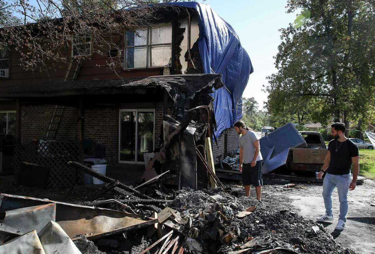 Alexander Molina, left, and his brother Samuel survey the damage to the home of their late mother Sunday, Nov. 15, 2020, in Shenandoah, Texas. Melanie Beach, their mother, died in May after battling cancer. The garage and part of the home burned in late October, the day after a memorial for her - which was delayed for months due to the COVID-19 pandemic.