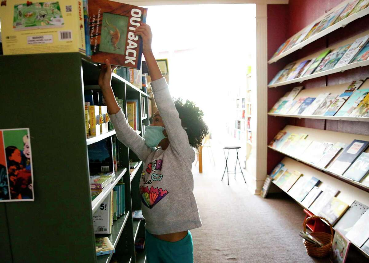 Delilah Greene, 7, puts a book back at River Oaks Bookstore while her mom, employee Whitney Andrews Corson, is interviewed at the Houston bookstore on Sunday, Nov. 15, 2020. After nearly forty-seven years, the locally-owned store is scheduled to close at the end of the year.