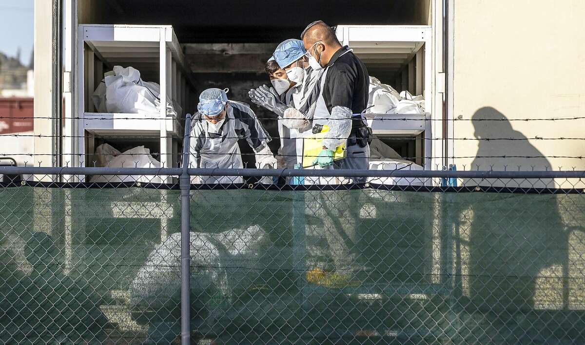 El Paso County Detention inmates, sheriff deputies and morgue staff move bodies to mobile morgue units on Nov. 14.