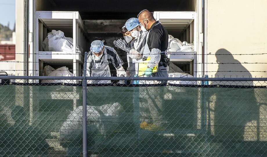 El Paso County Detention inmates, sheriff deputies and morgue staff move bodies to mobile morgue units on Nov. 14. Photo: Ivan Pierre Aguirre