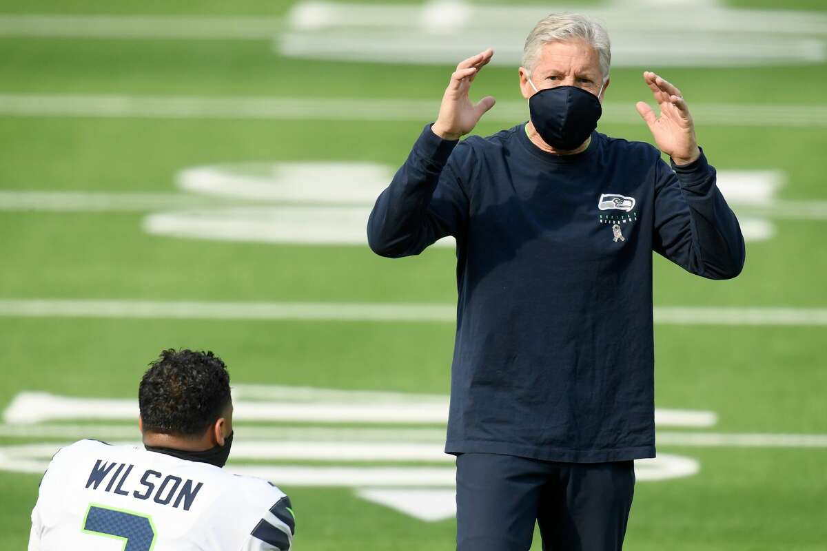 INGLEWOOD, CALIFORNIA - NOVEMBER 15: Head coach Pete Carrol of the Seattle Seahawks talks quarterback Russell Wilson prior to their game against the Los Angeles Rams at SoFi Stadium on November 15, 2020 in Inglewood, California. (Photo by Harry How/Getty Images)