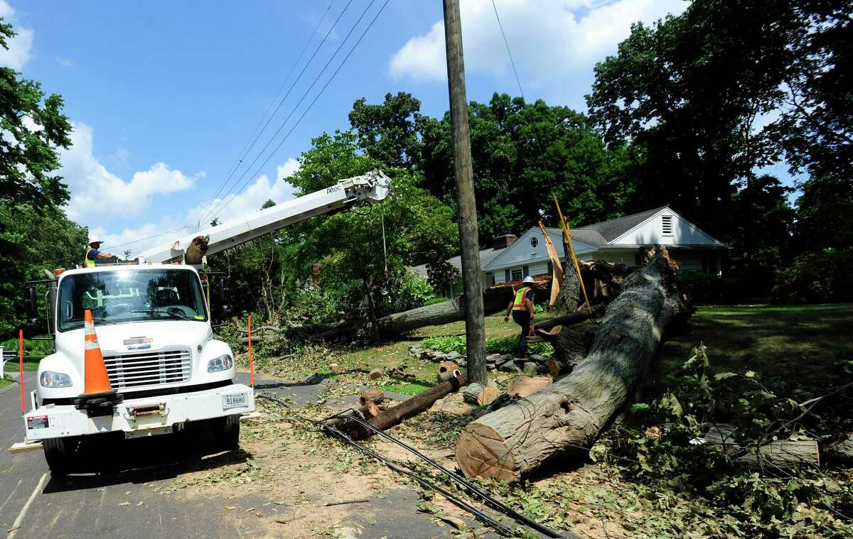 A file photo of a utility crew clearing a broken utility pole after damaging winds hit Connecticut.
