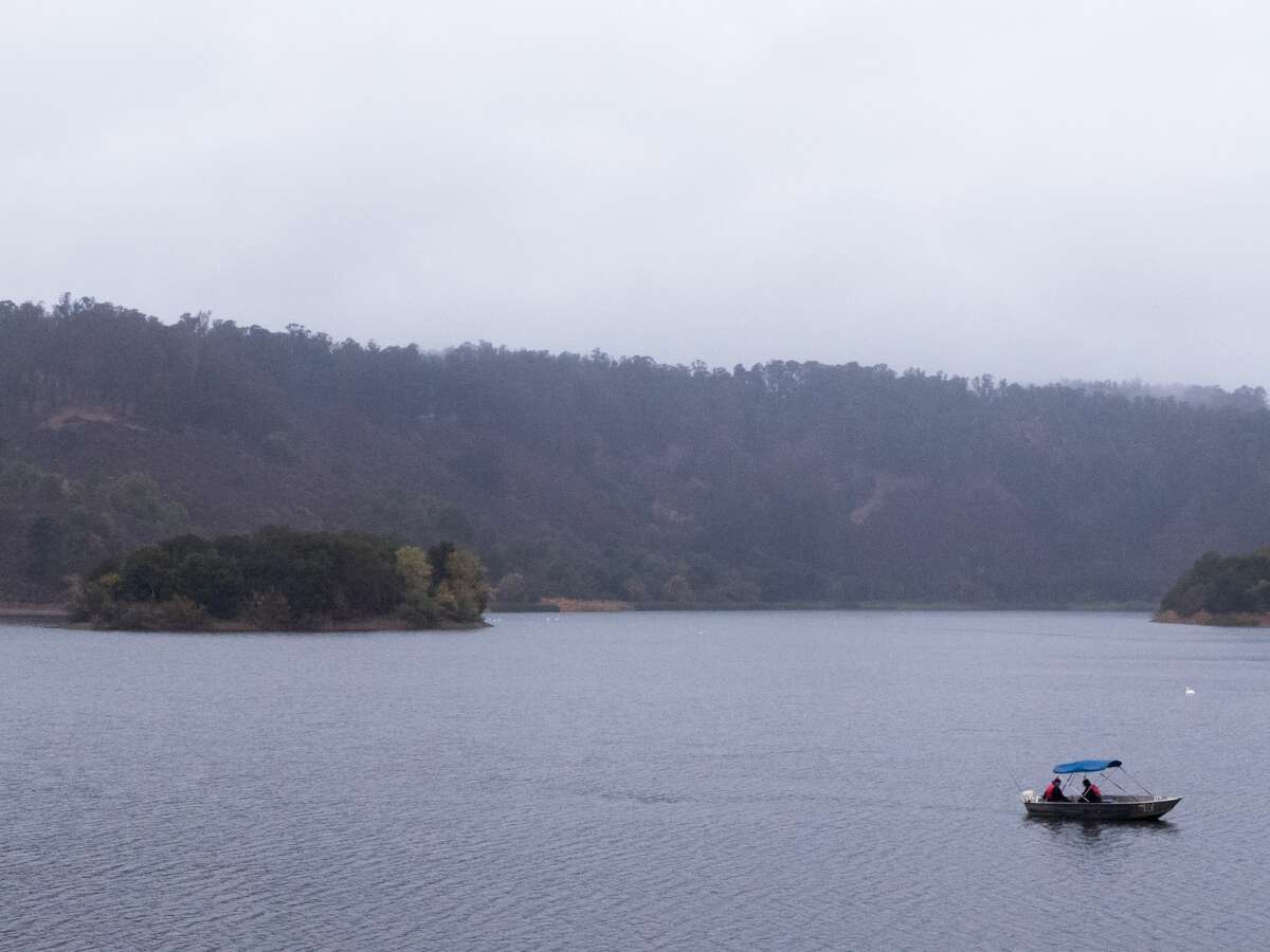 People fish on Lake Chabot during a rain shower in Oakland, Calif. on Nov. 13, 2020.