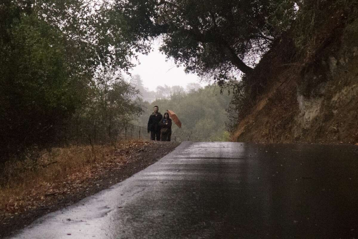 A couple walks along Lake Chabot during a rain shower in Oakland, Calif., on Nov. 13, 2020.