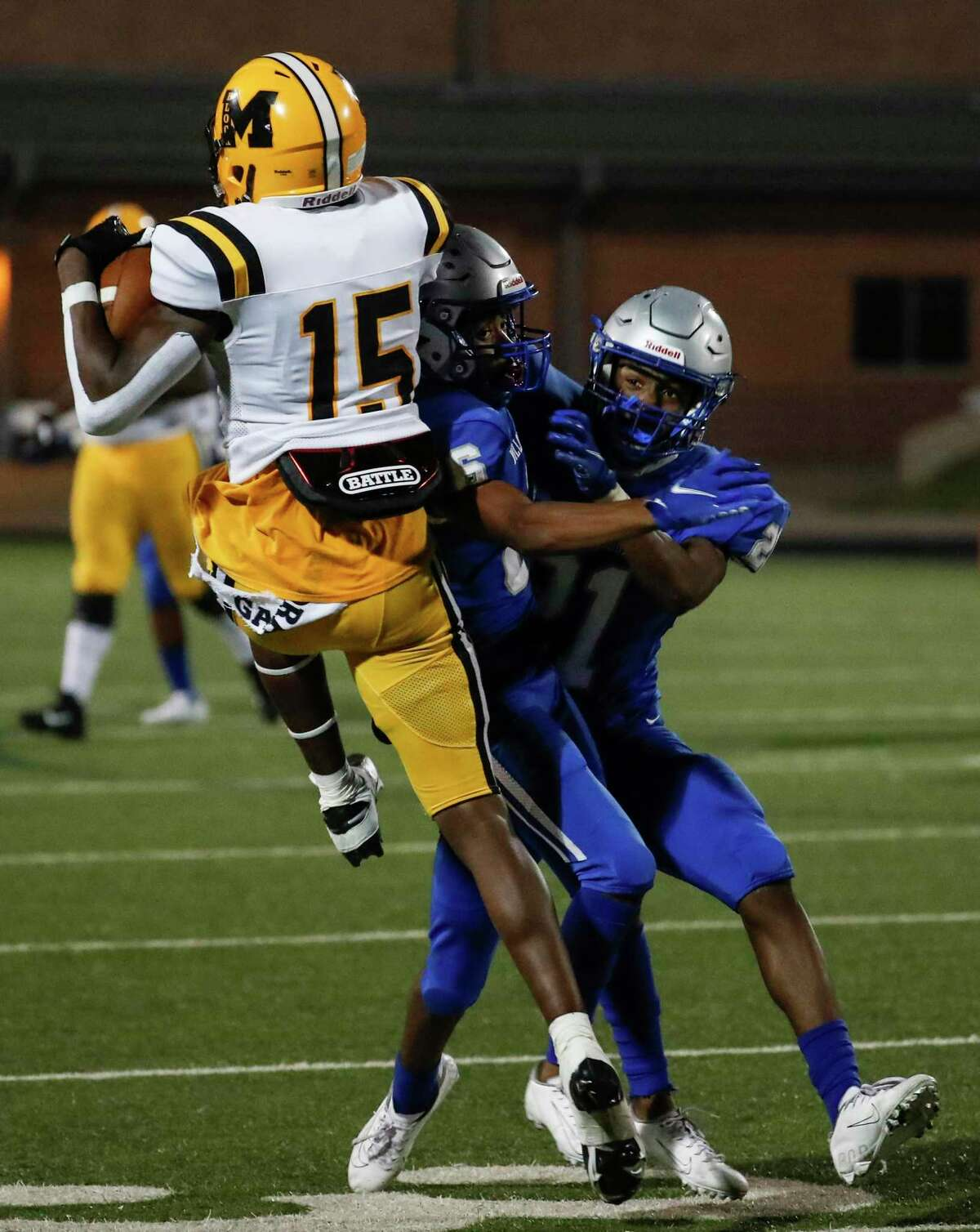 Fort Bend Marshall wide receiver Chris Marshall (15) turns to make a first down reception against Willowridge defensive backs Je'von Johnson and Kalem Williams (21) during an 11-5A matchup at Hall Stadium Thursday, Nov. 12, 2020 in Missouri City.