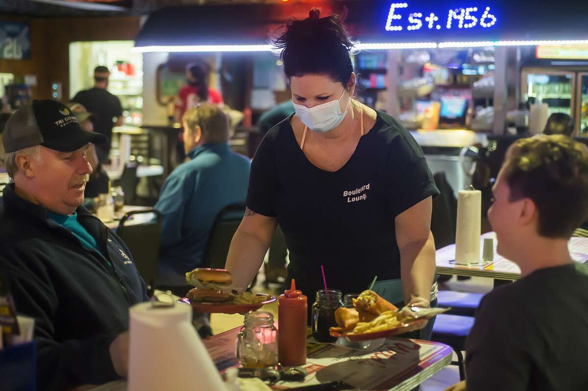 Marcy DeMoines serves lunch to a table of customers at the Boulevard Lounge on Monday, Nov. 16, 2020, one of the last few days of dine-in service before Gov. Whitmer's COVID-19 restrictions take effect. (Katy Kildee/kkildee@mdn.net)