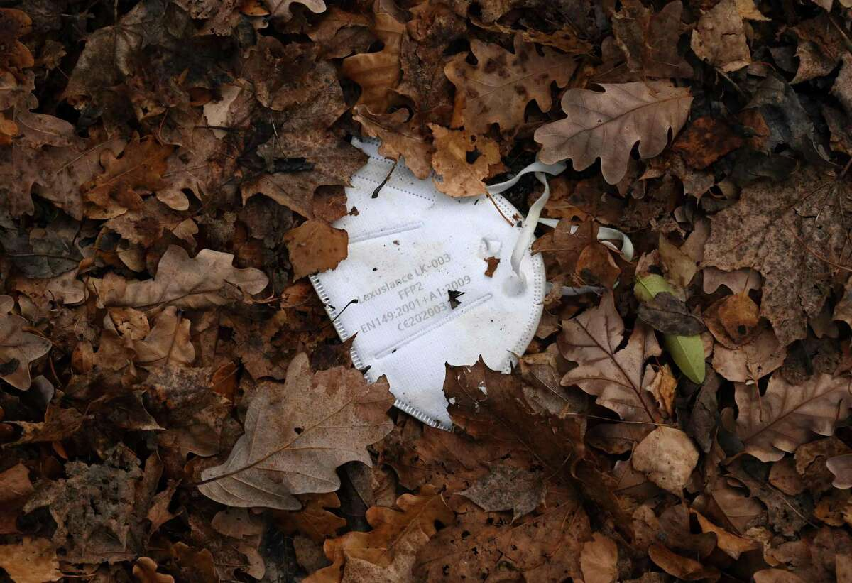 A discarded mask lies in the autumn leaves on a street in Eichenau, southern Germany, on November 16, 2020, amid the ongoing novel coronavirus Covid-19 pandemic. (Photo by Christof STACHE / AFP) (Photo by CHRISTOF STACHE/AFP via Getty Images)