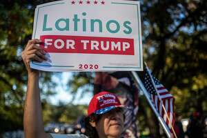 """A man holds up a """"Latinos for Trump"""" sign at a protest after Joe Biden won the 2020 presidential election in Austin, Texas on November 7, 2020. (Photo by Sergio FLORES / AFP)"""