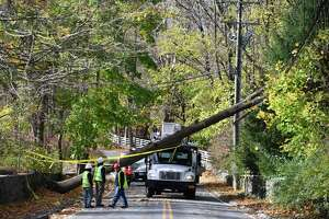 Crews clear a downed tree perched atop powerlines on Lower Cross Road in Greenwich, Conn. Monday, Nov. 16, 2020. Wind gusts from Sunday's storm exceeded 70 mph downing trees throughout town.
