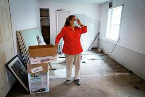 Valeria Tamez walks through her Harvey-damaged home, Friday, Nov. 13, 2020, in southeast Houston. The foundation of the house is severely damaged and cracks can be seen on the floor, walls and the ceiling. Tamez was recently notified by the city that her application for housing relief would have to move from the city's program to one being run by the state's General Land Office.