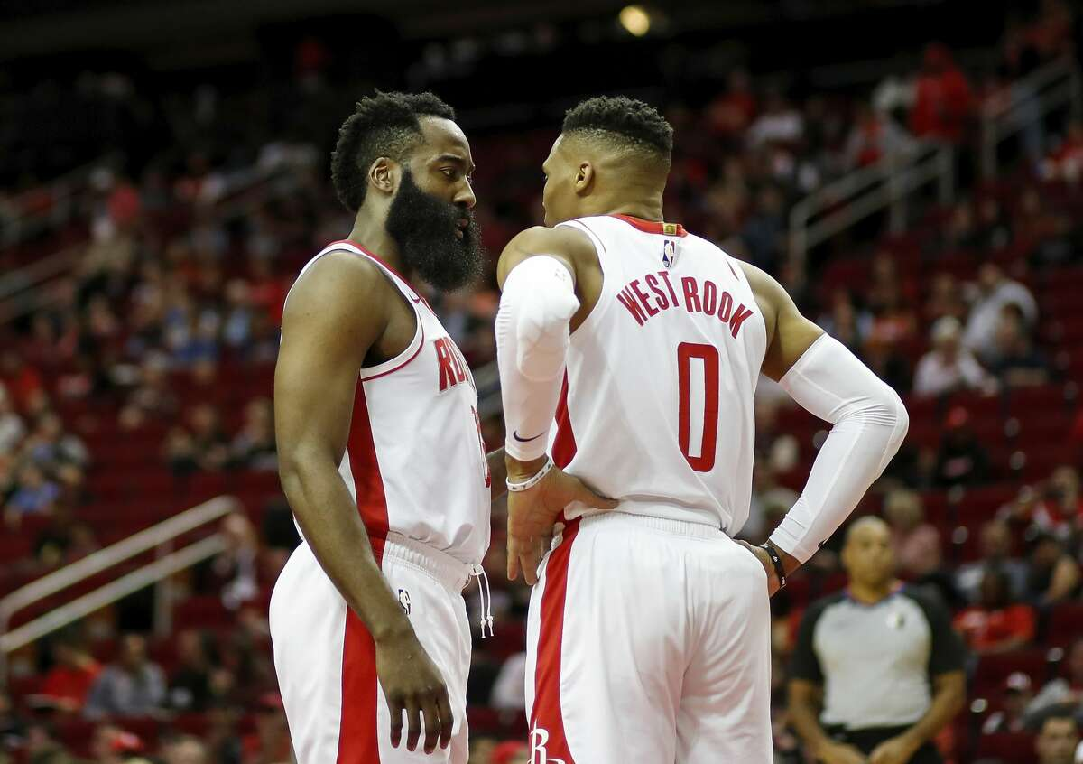 James Harden of the Houston Rockets talks with Russell Westbrook in the first half against the Orlando Magic at Toyota Center on March 08, 2020 in Houston, Texas.