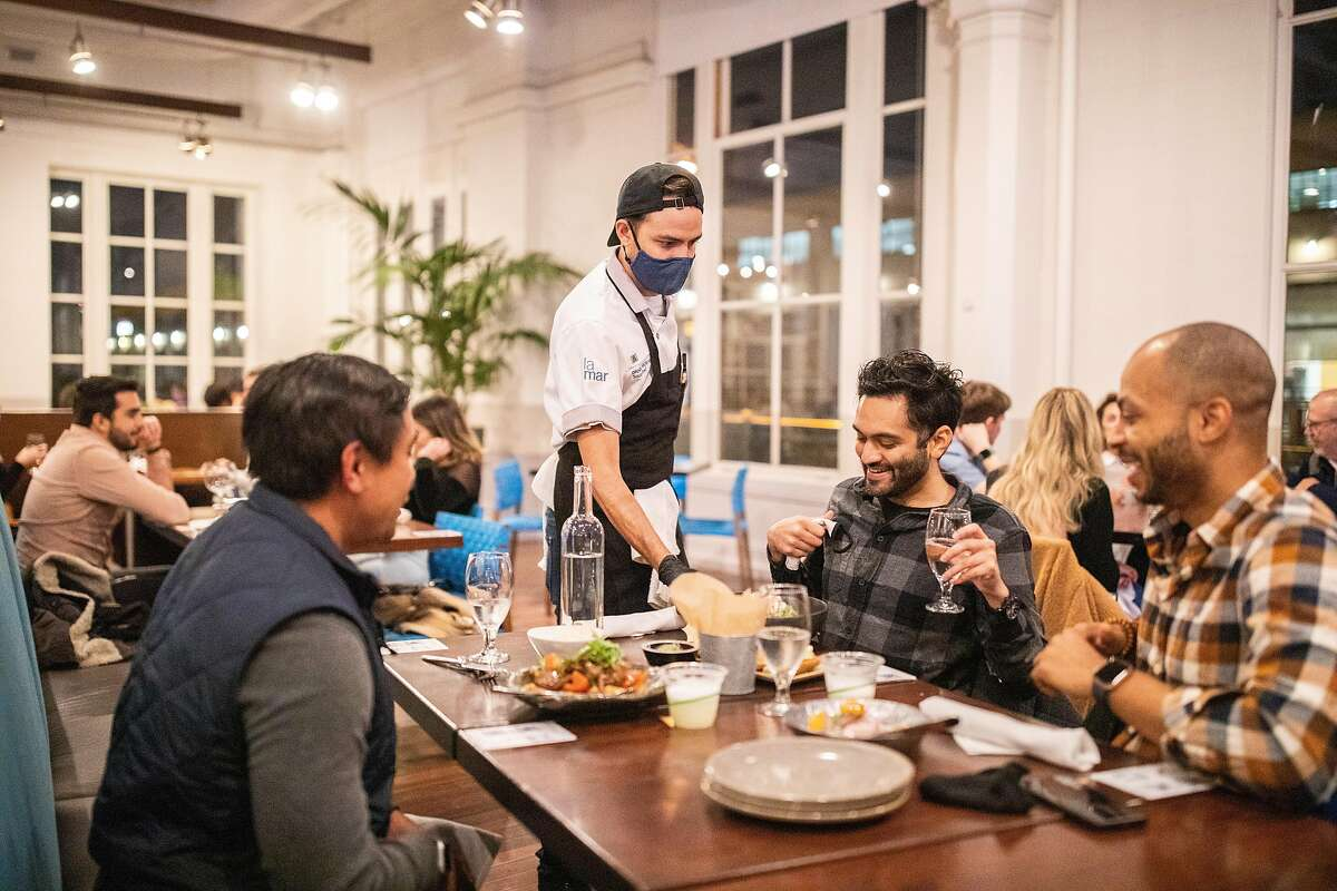 Daniel Morales serves diners at La Mar on Friday, the final day of indoor dining in San Francisco. Gov. Gavin Newsom announced other counties, including Alameda and Napa, will need to stop indoor dining as well.