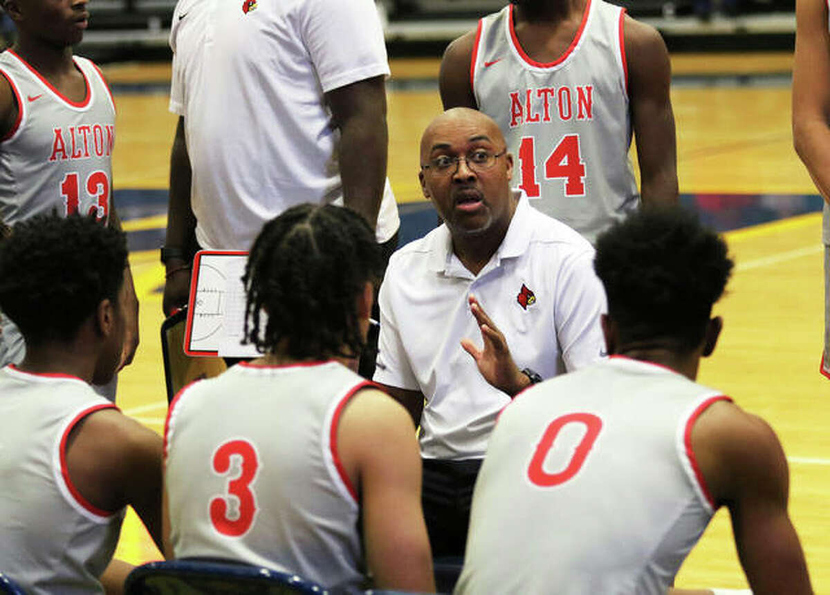 Alton coach Dana Morgan (center) talks with his team during a timeout during a Redbirds victory over Paducah (Ky.) Tilghman on Dec. 7 at the Marion Shootout last season in Marion. Morgan opened his second season with the Redbirds on Monday when teams in Illinois were allowed to hold their first practice.