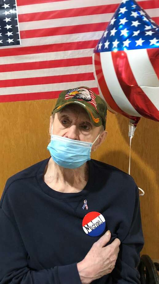 Candlewood Valley Health & Rehabilitation in New Milford recently honored its veterans with gifts. Veterans received a balloon, pins, an American flag and a special dessert. Above, Michael Moran, who served in the field artillery division of the Army, proudly acknowledges his service beneath his mask and alongside a balloon. Photo: Courtesy Of Candlewood Valley Health & Rehabilitation / Danbury News Times Contributed