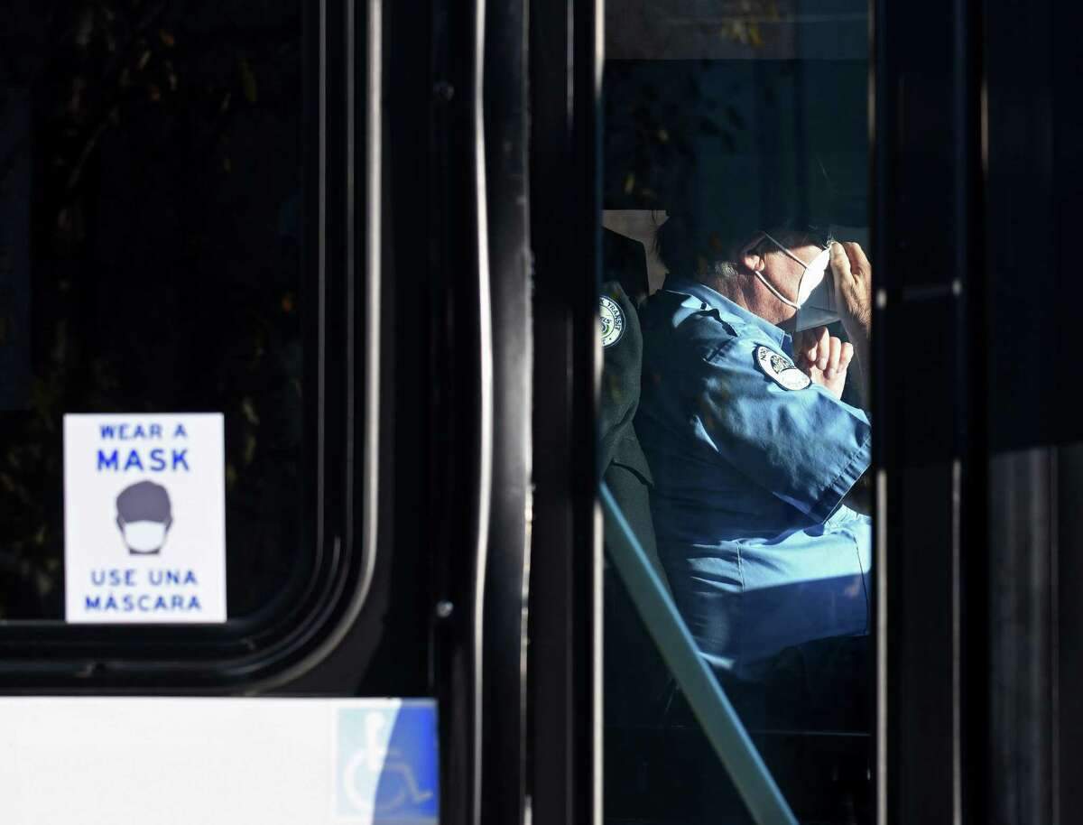 A bus driver wears a mask as free masks are distributed at the Norwalk Transit District hub in Norwalk, Conn. Monday, Nov. 16, 2020.
