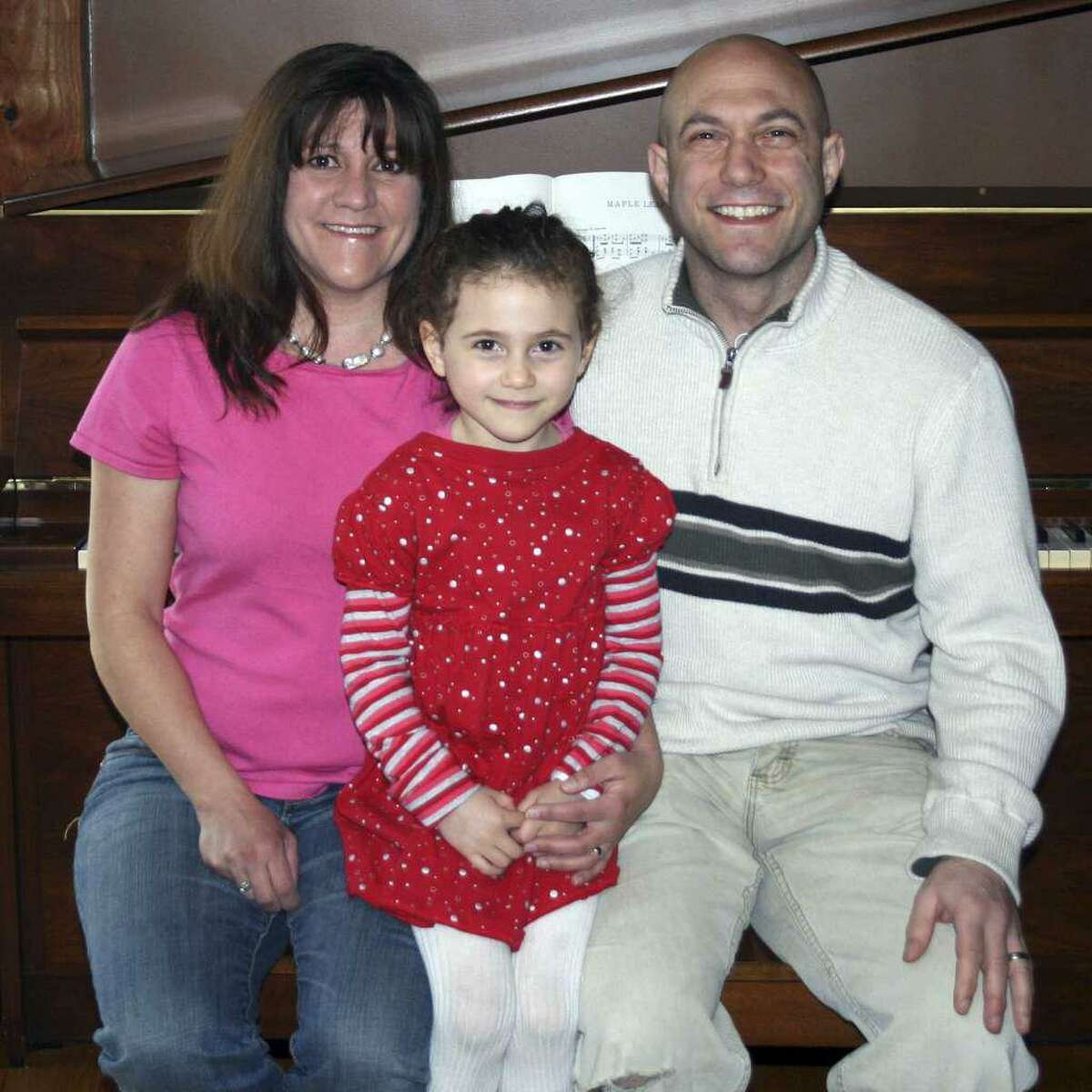 This April 2012 file photo provided by the family shows Avielle Richman, center, with her parents Jennifer Hensel and Jeremy Richman in Boston. Avielle was among the 20 children killed in the Dec. 14, 2012 Sandy Hook Elementary School shooting in Newtown.