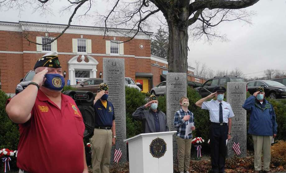 From left, Tom Moore, Bill Glass, Frank Dunn, Paul Sullivan, Bing Ventres and Frank Dahm salute the flag during the National Anthem at a Veterans Day ceremony in Wilton, CT, on Nov. 11, 2020. Photo: Jeannette Ross / Hearst Connecticut Media / Wilton Bulletin