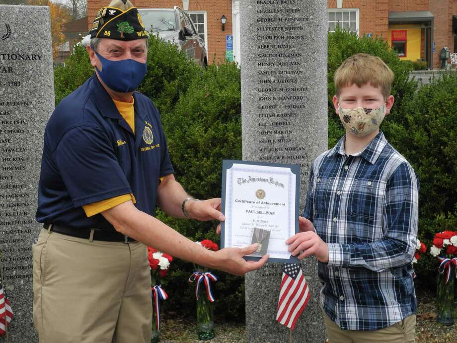 American Legion Post Commander Bill Glass presents a medal and a certificate to Paul Sullivan, a sixth grader at Middlebrook School, at the Veterans Day ceremony on Nov. 11, 2020. Paul won the post's annual Veterans Day essay contest. Photo: Jeannette Ross / Hearst Connecticut Media / Wilton Bulletin