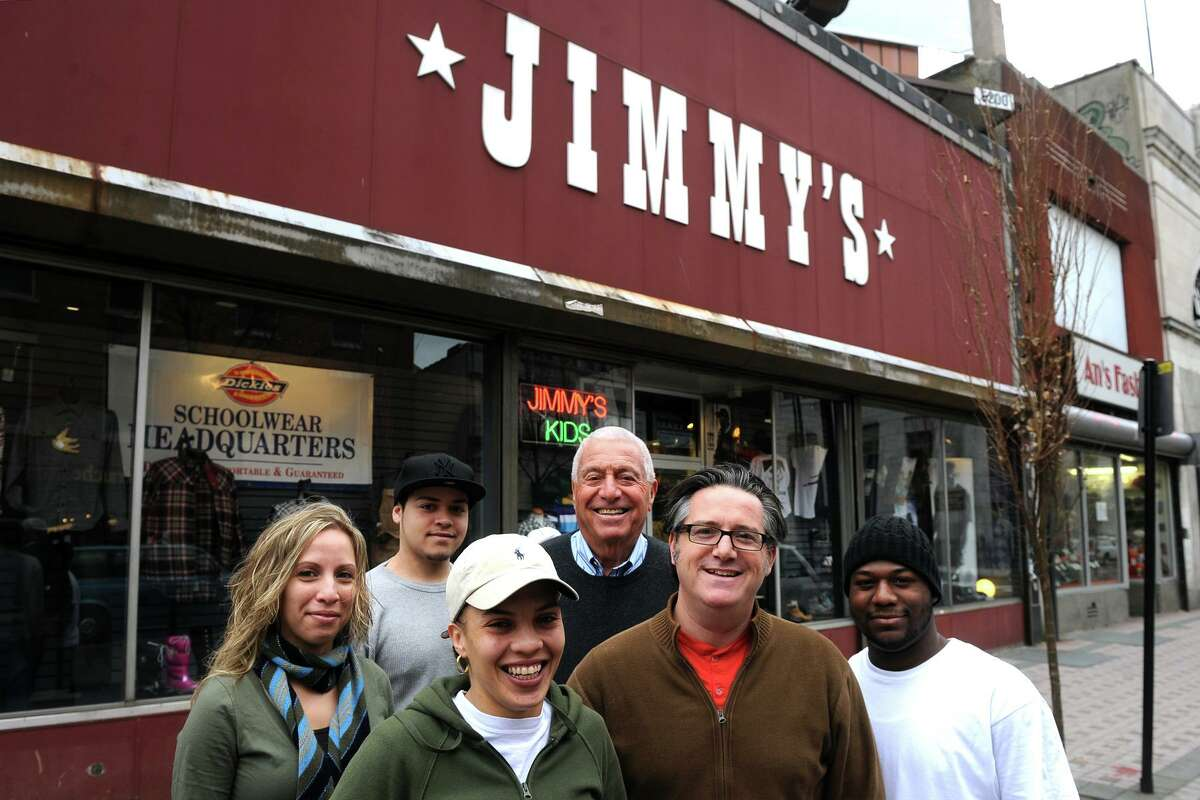 """Bob Schneider and his son Dave (center) stand in front of Jimmy's Hip Hop with store employees (from left) Jasmin Guzman, Steven Nieves, Jacenia Guzman and Fidel Hernaiz, Nov. 30th, 2010. Jimmy's was opened as an Army and Navy surplus store on Main Street in Bridgeport in 1920 by Bob's father Max """"Jimmy"""" Schneider."""