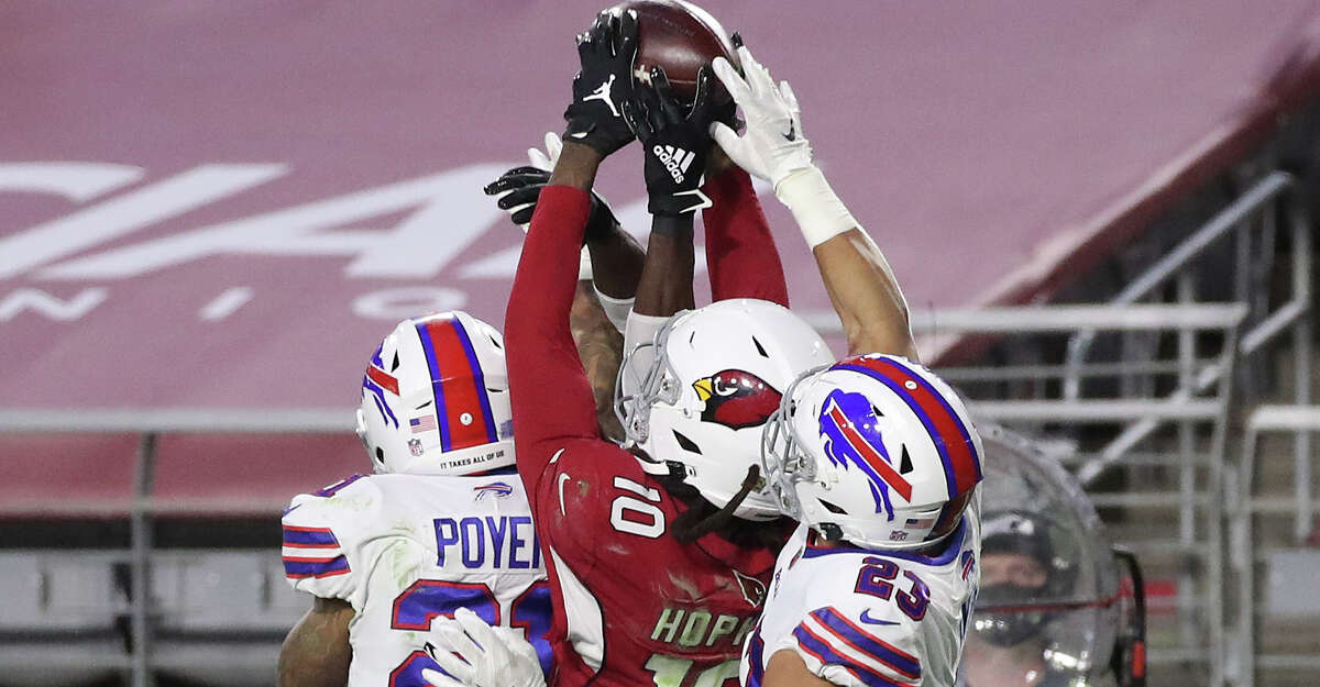 Wide receiver DeAndre Hopkins #10 of the Arizona Cardinals catches the game-winning touchdown pass as safety Jordan Poyer #21 and safety Micah Hyde #23 of the Buffalo Bills defend during the final seconds of the fourth quarter at State Farm Stadium on November 15, 2020 in Glendale, Arizona. (Photo by Christian Petersen/Getty Images)