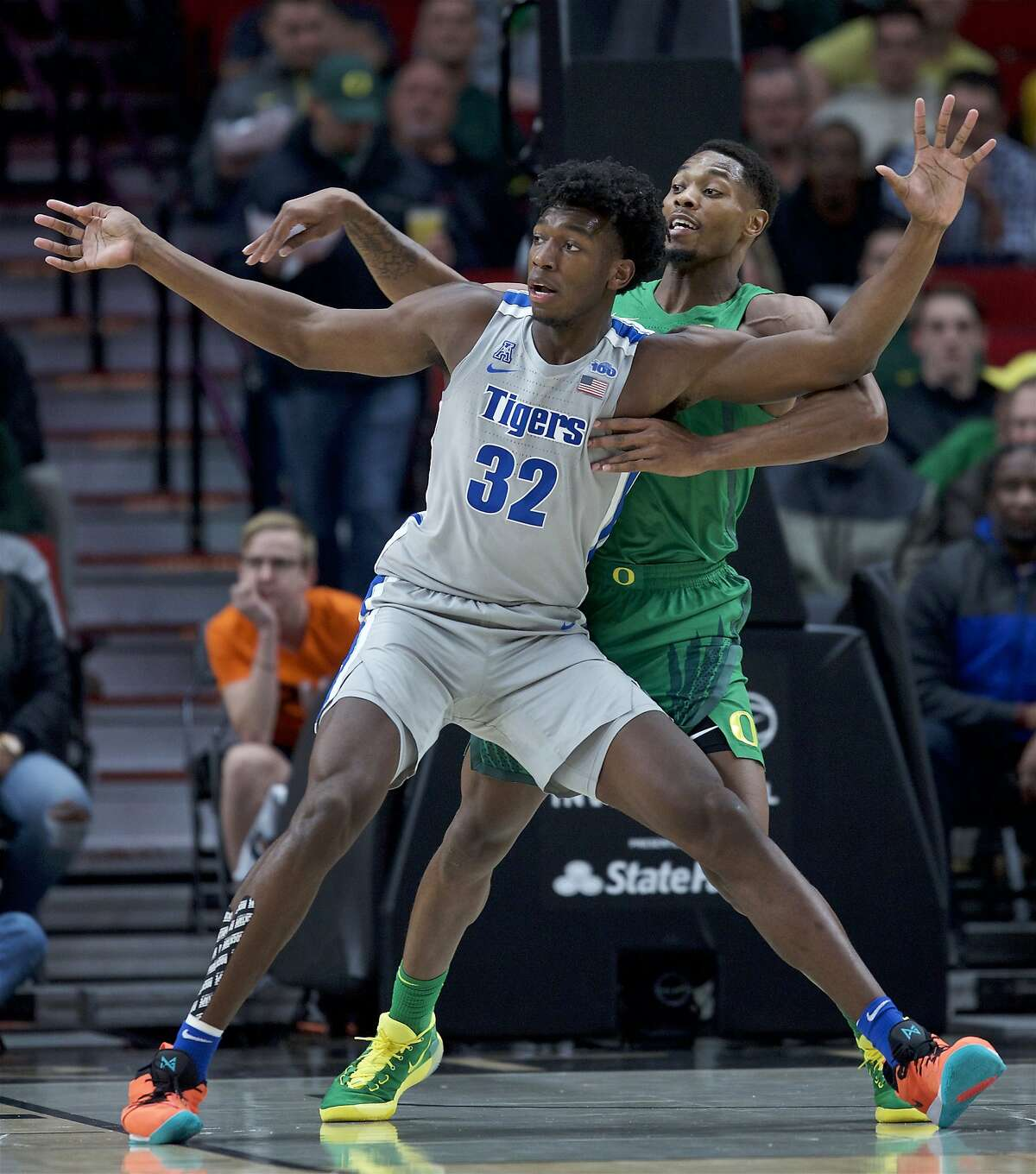 FILE - Memphis center James Wiseman (32) posts up against Oregon forward Shakur Juiston during the first half of an NCAA college basketball game in Portland, Ore., in this Tuesday, Nov. 12, 2019, file photo. At long last, James Wiseman is about to be on a team again. More than a year removed from the end of his three-game college career that was doomed almost before it started because of NCAA rulings regarding his eligibility, the 7-foot-1 left-hander will be one of the first players selected in Wednesday's, Nov. 18, 2020, NBA draft. It's hard to envision a scenario where he doesn't go in the first three picks, which are currently held by Minnesota, Golden State and Charlotte. (AP Photo/Craig Mitchelldyer, File)