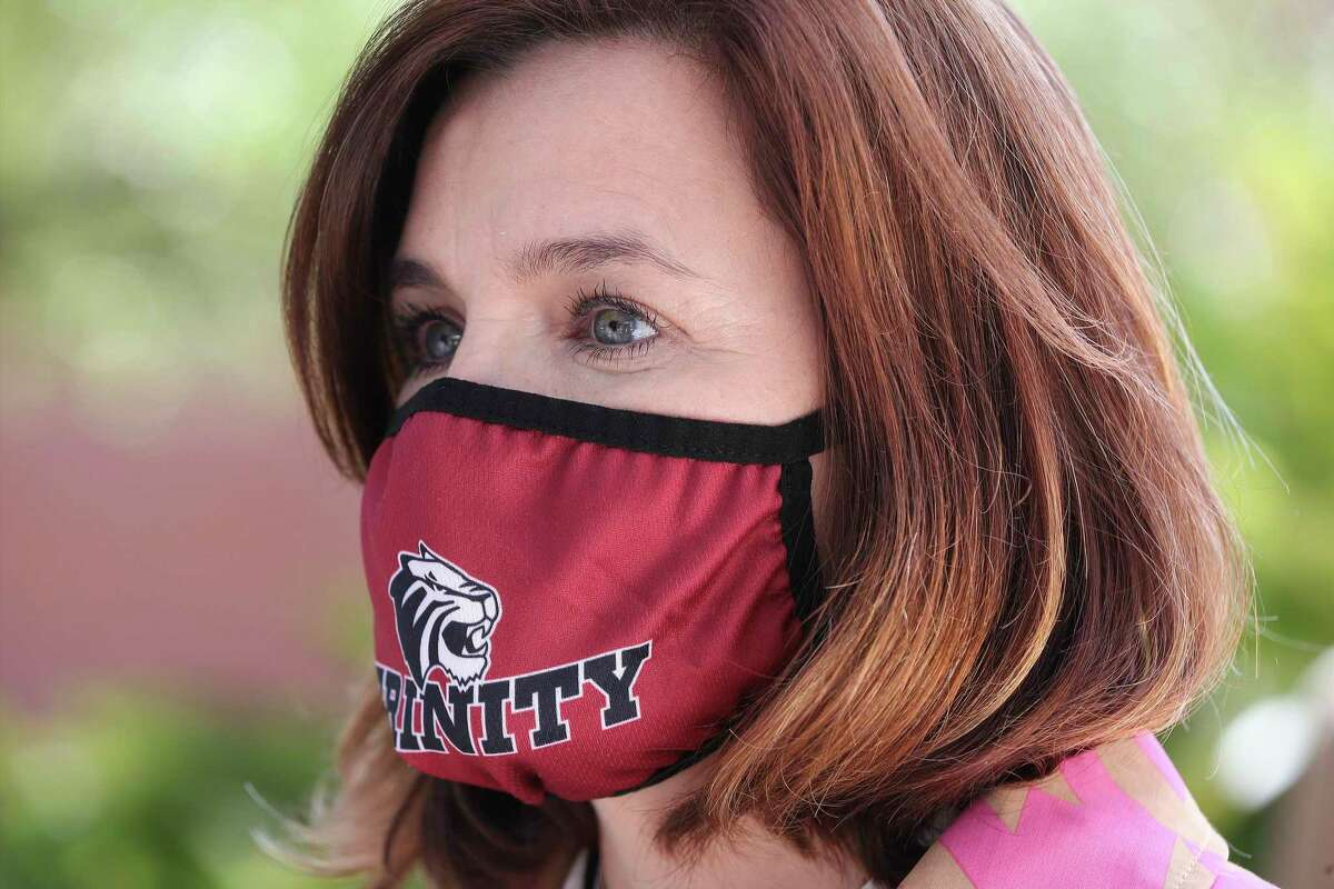 Trinity University spokesperson Tess Coody-Anders wears a mask emblazoned with the school name at a news conference on Monday, Nov. 16, 2020.