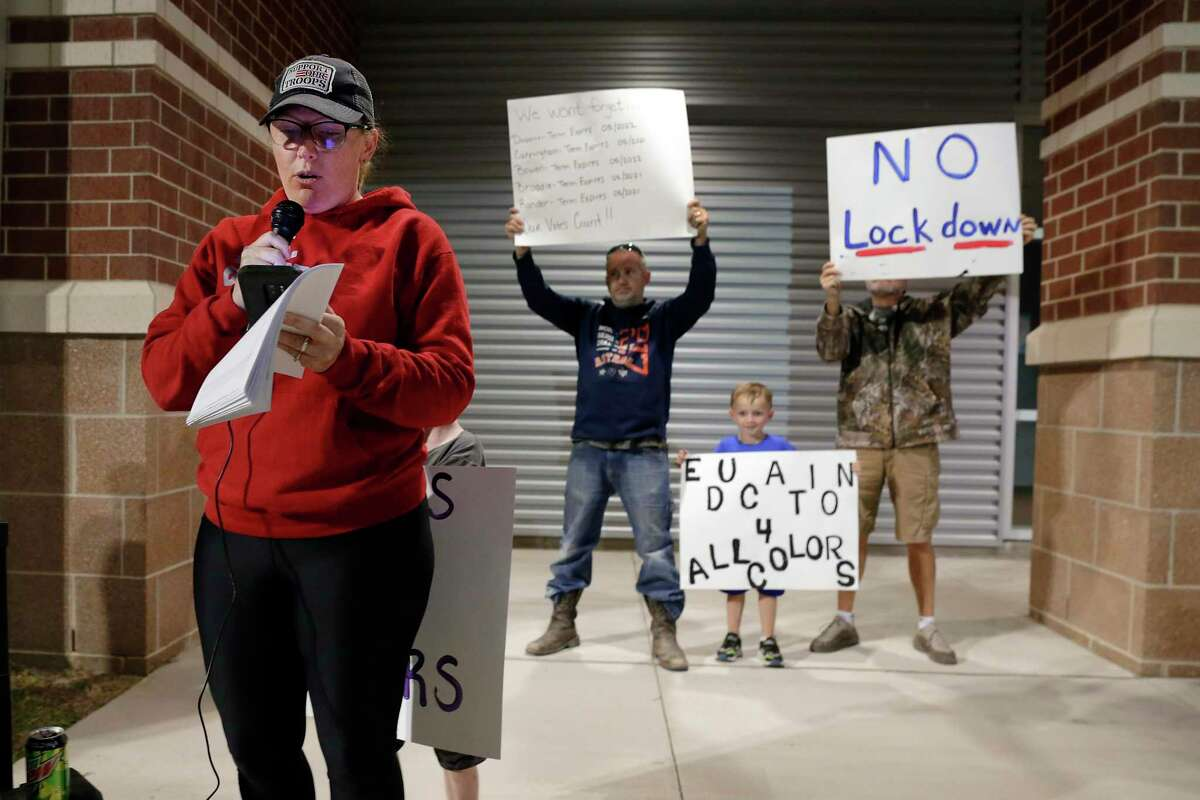 Mandy Feltner, (in red) mother of four, speaks as it's live cast on Facebook, along with other parents and community members protesting the choice of Eric Williams as the new superintendent outside of the Clear Creek ISD board meeting, moved from the district headquarters to six miles away at the Challenger Stadium Fieldhouse Monday, Nov. 16, 2020 in Webster, TX.