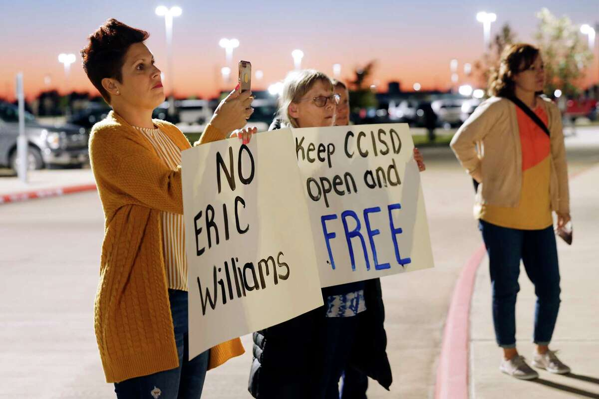 Parents and community members, protesting the choice of Eric Williams as new superintendent, gather with signs outside of the Clear Creek ISD board meeting, moved from the district headquarters to six miles away at the Challenger Stadium Fieldhouse Monday, Nov. 16, 2020 in Webster, TX.